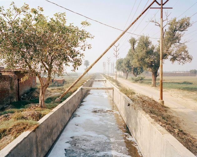 Polluted water flows through an irrigation channel used to feed the crops in the agricultural belt surrounding Kanpur's industrial heartland.