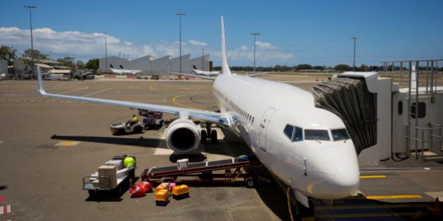 Jet aeroplane being loaded while waiting for boarding passengers at a terminal gate
