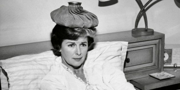 Mid adult woman reclining on the bed with an ice pack on her head