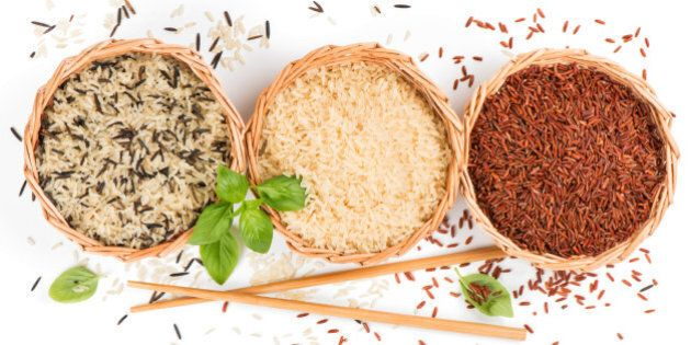 Top view of different rice types in a baskets decorated with basil and chopsticks isolated on white