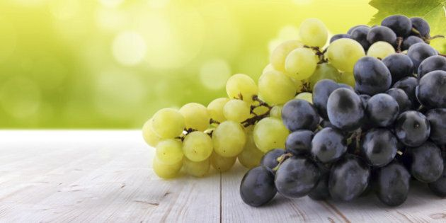 Wine collection: White and red grapes on table in vineyard. Blurred lights in