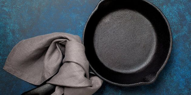 Empty cast-iron frying pan on a blue background (top view)