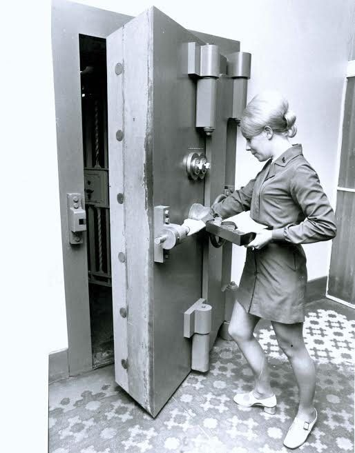 1960-1970: this lady wore the beehive beautifully as she posted for a photo at the State Bank, opening a safe.