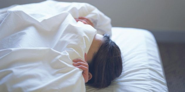 Woman lying in bed covering face with