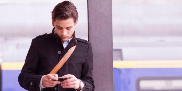 Man on train platform checks cell phone
