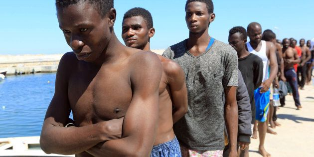 JULY 8, 2017: Illegal migrants from Africa, attempting to reach Europe, walk towards a detention center...