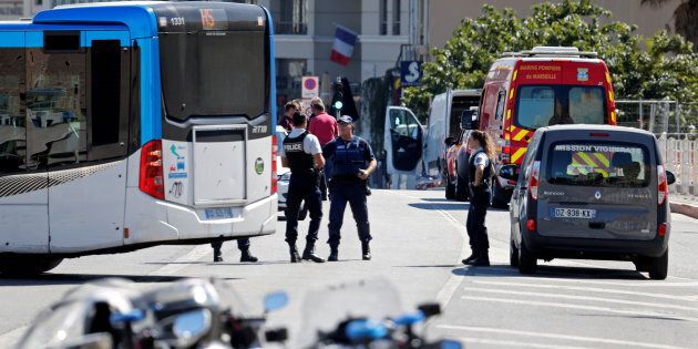 French police secure the area where one person was killed and another injured after a car crashed into...