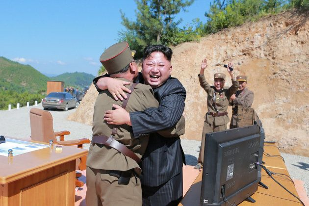 North Korean leader Kim Jong Un reacts with scientists and technicians of the DPRK Academy of Defence...