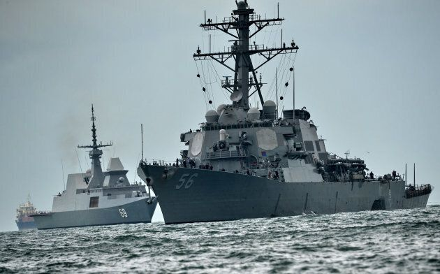 The guided-missile destroyer USS John S. McCain (R), with a hole on its