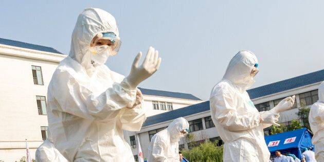 Health workers act in an exercise dealing with an outbreak of H7N9 avian flu on June 17 in Hebi, China.