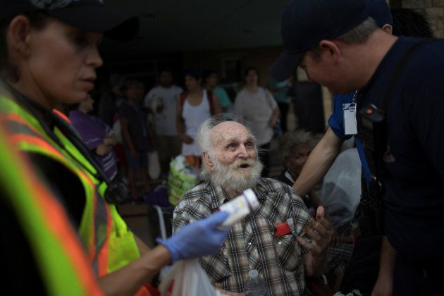 A man is assisted by medics as he is evacuated after losing his home to Hurricane Harvey in Rockport,