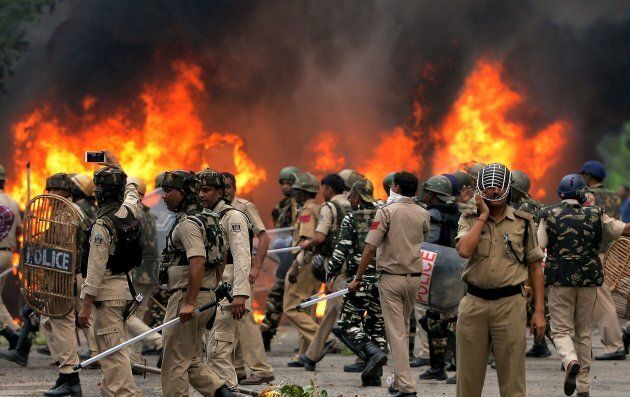 Indian security forces walk next to burning vehicles set alight by rioting followers of a religious leader...
