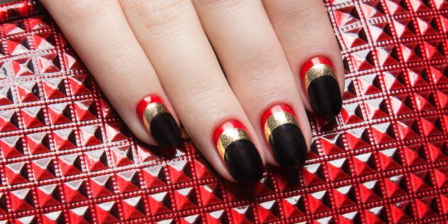 Beautiful women's manicure with black, red, gold polish on the nails. Picture taken in the studio. Close-up.