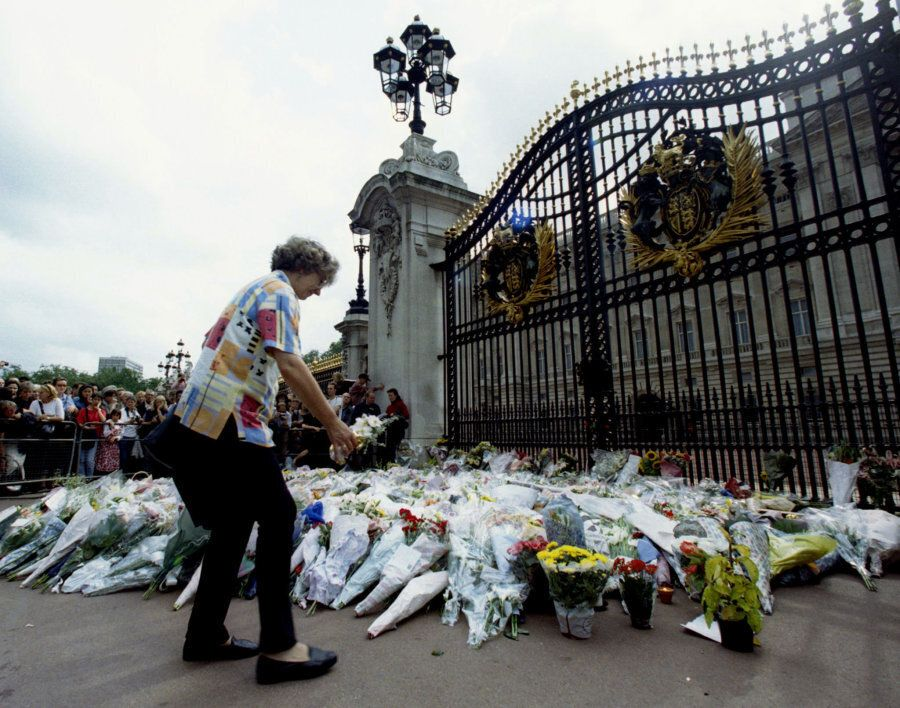 A woman adds another bouquet of flowers to the growing floral tribute outside Buckingham Palace August...