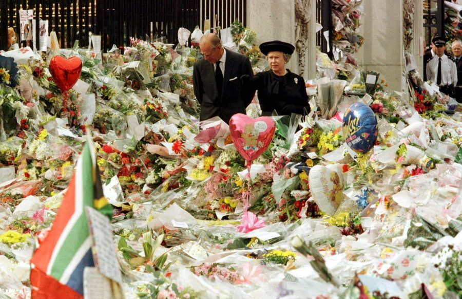 Queen Elizabeth and the Duke of Edinburgh look at floral tributes laid outside Buckingham