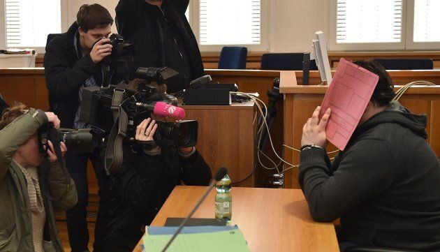 Former nurse Niels Hoegel hides he face from the media during the 2014 trial for two