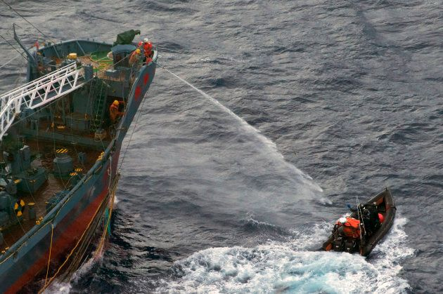 A water canon is sprayed from a Japanese whaling ship towards a small Sea Shepherd boat, about 480 km...
