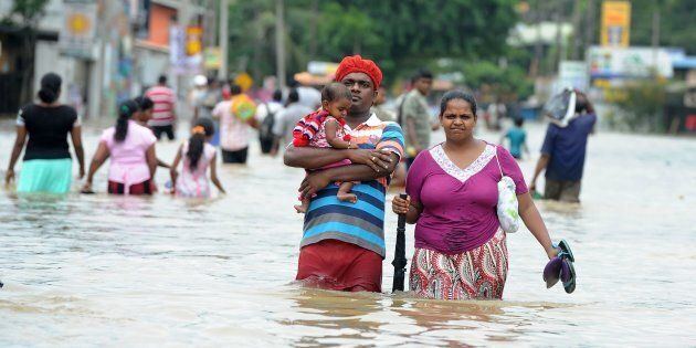 TOPSHOT - A Sri Lankan couple with their child make their way through floodwaters in the suburb of Kaduwela in capital Colombo on May 17, 2016. Emergency workers in Sri Lanka on May 17 found the bodies of a woman and two children killed in a landslide, taking the toll from two days of heavy rain to 11, with thousands more forced to flee their homes.  / AFP / LAKRUWAN WANNIARACHCHI        (Photo credit should read LAKRUWAN WANNIARACHCHI/AFP/Getty Images)
