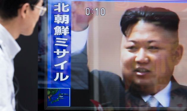 A pedestrian walks past a monitor showing an image of North Korean leader Kim Jong-Un in a news program...