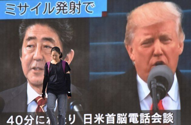 A woman walks in front of a huge screen displaying Japanese Prime Minister Shinzo Abe and U.S. President...