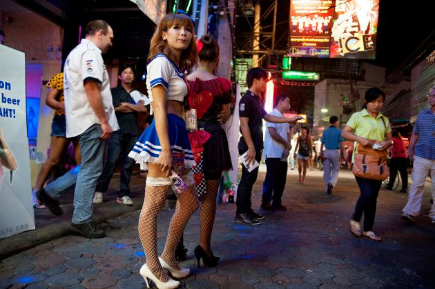 Thai women in cosplay uniforms stand outside the brothels of Pattaya
