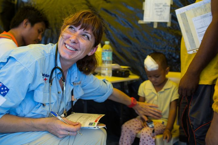 Paramedic Abigail Trewin with a young patient in a hospital built in Tacloban, the Philippines after a typhoon.