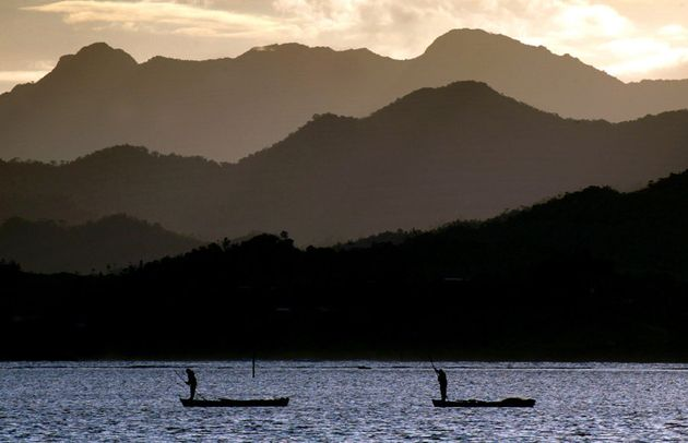 Fijian fishermen stand in their boats in