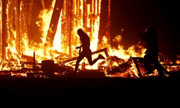 A Burning Man participant evades a chasing firefighter and runs into the flames of the