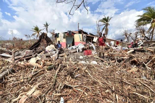 People stand next to their destroyed house in Les Cayes, Haiti following Hurricane Matthew. Haiti faces...