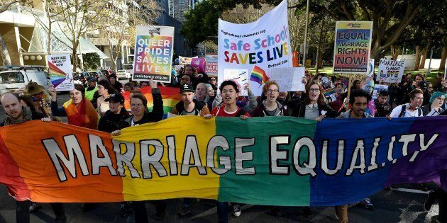 Pro-gay marriage supporters carry a rainbow banner and flags during a rally in Sydney on June 25,