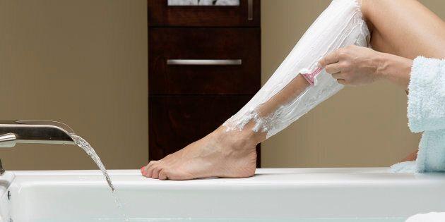Caucasian woman shaving her legs at bathtub
