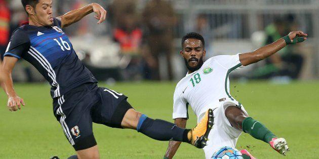 Saudi Arabia's Nawaf Alabid fights for the ball against Japan's Hotaru
