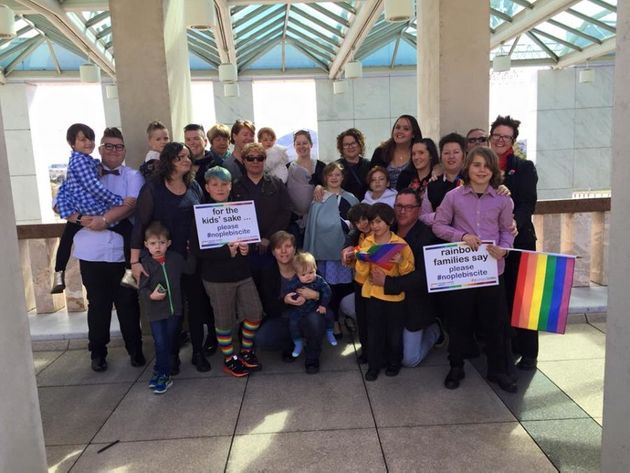 The Rainbow Families group in Canberra on Tuesday; Callum (blue hair, holding sign), Sadie (grey shawl,...