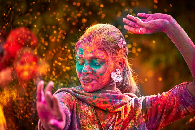 A young Indian woman dancing during Holi Festival.