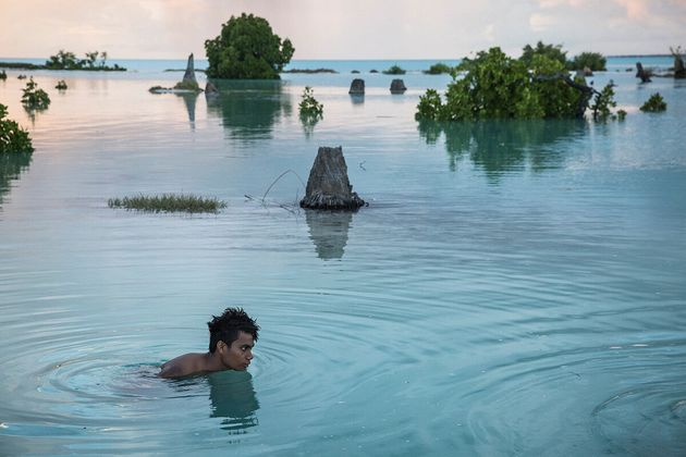 Peia Kararaua, 16, swims in the flooded area of Aberao village. Kiribati is one of the countries most...