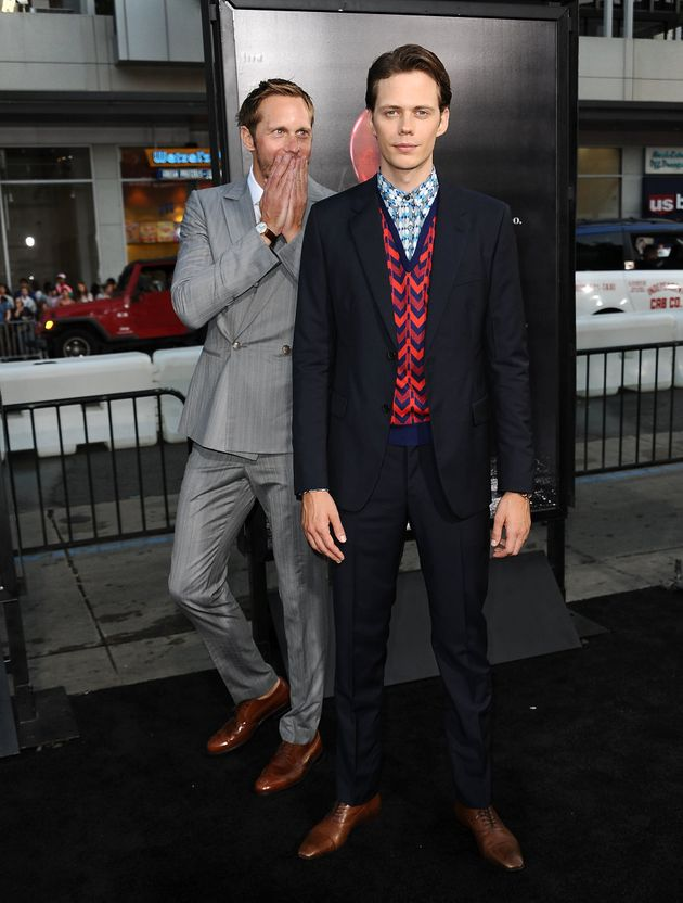 Taking things very seriously, big brother Alexander walks the red carpet with brother