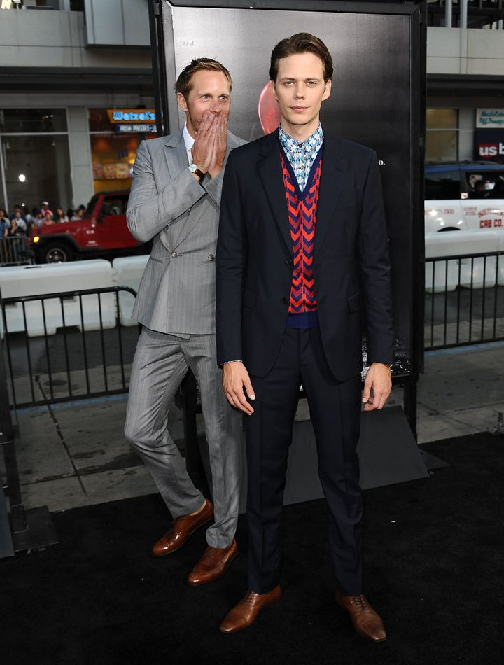 Taking things very seriously, big brother Alexander walks the red carpet with brother Bill.