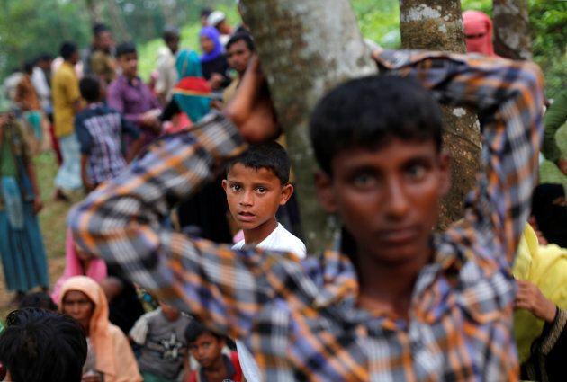 Rohingya refugees wait near Kutupalong refugee camp after crossing the Bangladesh-Myanmar border.