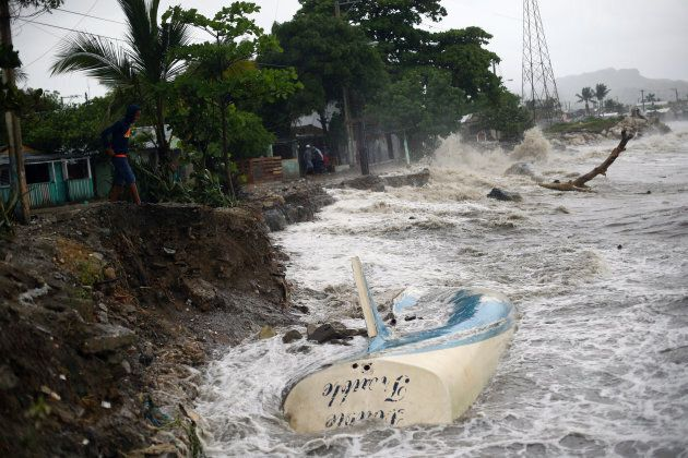 Waves crash against the shore and a stranded boat as Hurricane Irma moves off from the northern coast of the Dominican Republic.