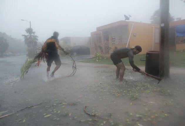 People pick up debris as Hurricane Irma howled past Puerto Rico.