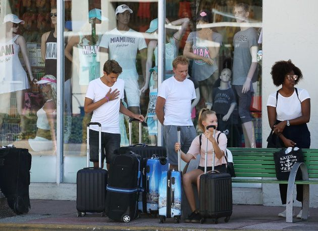 People wait with their luggage at a bus stop as Miami Beach announced a mandatory evacuation ahead of the approaching Hurricane Irma.