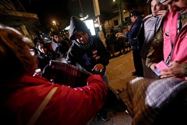 People gather on a street as they receive blankets after an earthquake hit Mexico City, Mexico, September...