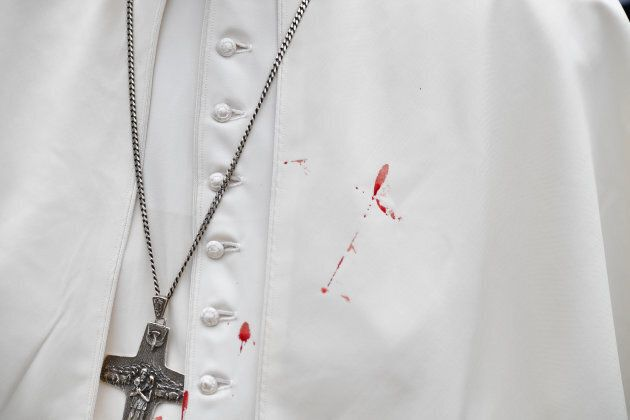 A few droplets of blood stain Pope Francis' white tunic.