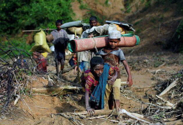 Rohingya refugees walk on a muddy path after crossing the Bangladesh-Myanmar border in Cox's Bazar, Bangladesh...