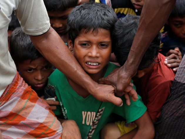 Rohingya refugee children are stopped by volunteers as they jostle to receive food distributed by local...