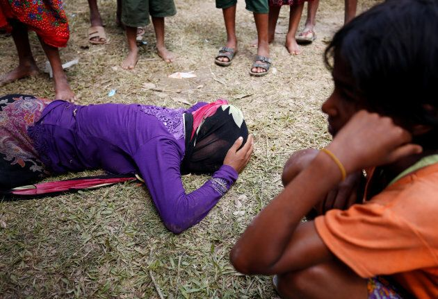 A Rohingya woman cries on the ground, as she received news, over the phone, that her husband was killed...