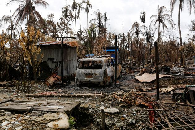A car is seen near a house that was burnt down during the last days violence in Maungdaw, Myanmar August...