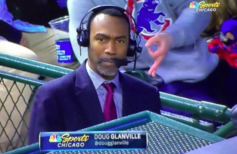 A fan in a gray sweatshirt flashes an alleged white power symbol behind NBC Sports Chicago reporter and former MLB player Doug Glanville. (Twitter/@Flipkin)