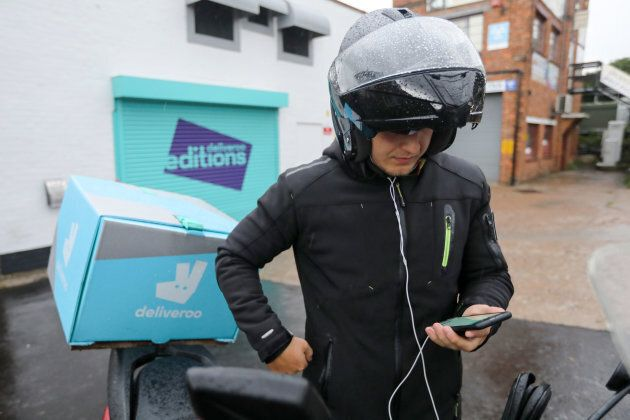 A Deliveroo delivery driver looks at an app on his smartphone