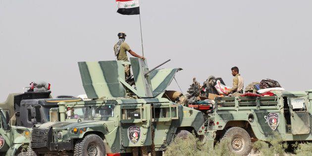 Iraqi security forces sit in military vehicles in the Nuaimiya suburb of Fallujah, Iraq, June 1, 2016. REUTERS/Alaa Al-Marjani